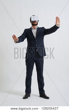 Businessman in a formal wear trying to push something wearing virtual reality glasses