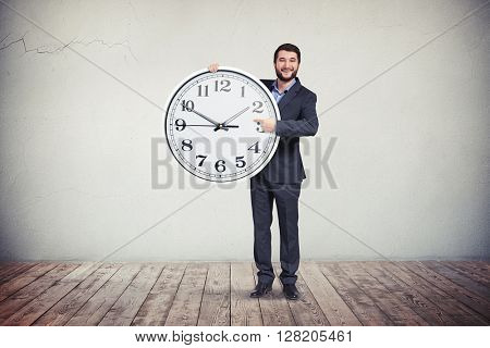 A smiling man in business suit is holding a big round clock and pointing at the time on it