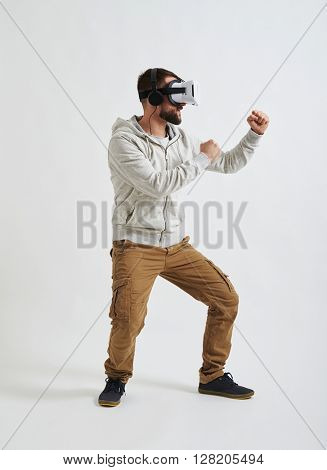 A young man in casual clothes and virtual reality glasses is standing in fighting pose