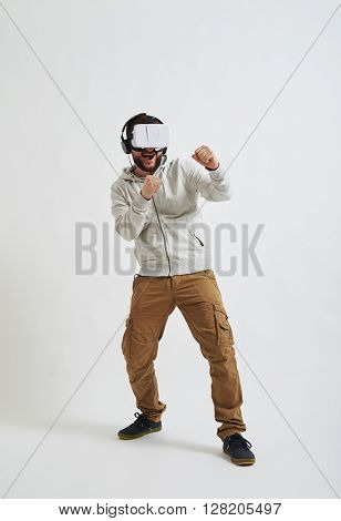 A young man in casual clothes and virtual reality glasses is boxing