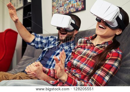 A young man and woman in casual clothes and virtual reality glasses surprised by virtual reality headset glasses