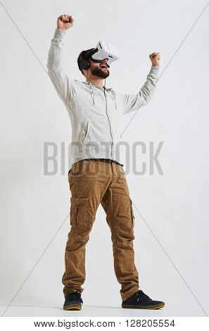 A young bearded man in casual clothes and virtual reality glasses looks joyful in 3d reality