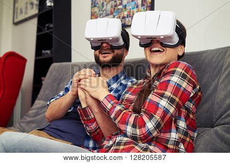 A young man and woman in casual clothes and virtual reality glasses is watching romantic movie