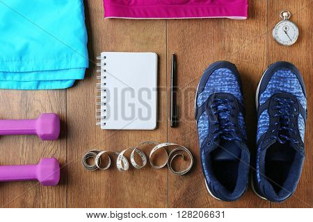 Athlete's set with female clothing, equipment and notebook on wooden background