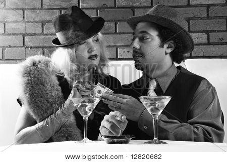 Caucasian prime adult retro male giving money to Caucasian prime adult retro female.