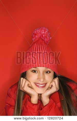 Portrait of Asian-American teen girl wearing winter hat resting head on hands against red background.