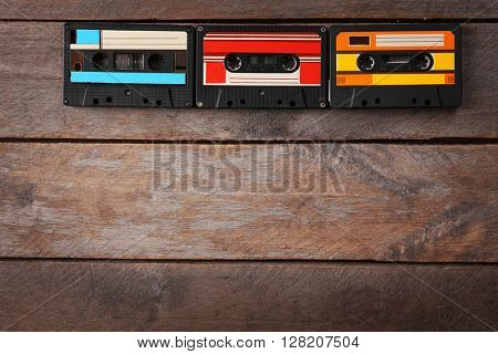 Group of retro cassettes on wooden table, copy space