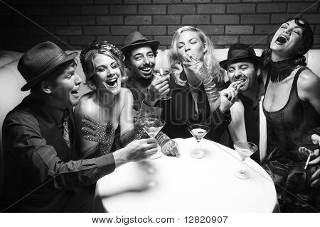 Group of Caucasian prime adult retro males and females sitting at table in lounge laughing.