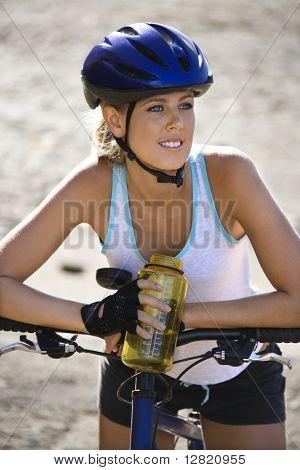 Mid-adult mujer caucásica llevaba casco de bicicleta, sentado en la bicicleta, sosteniendo la botella de agua.