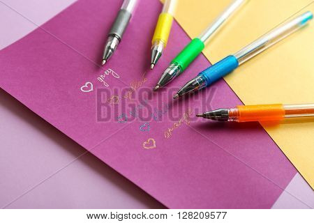 Set of colored pens on paper background