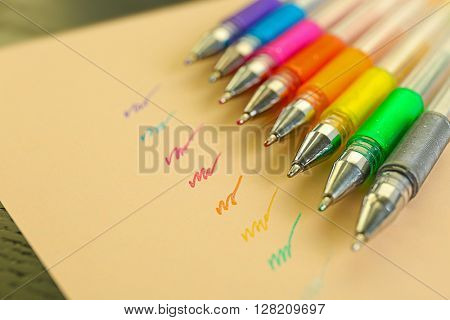 Set of colored pens on beige paper