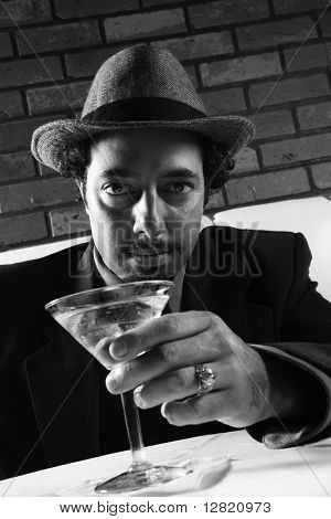 Caucasian prime adult male in retro suit sitting at table with martini looking at viewer.