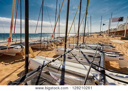 Catamaran empty. Catamaran stored on beach in La Baule France on blue sky.