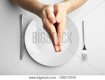 Male holding hands together over plate, isolated on white