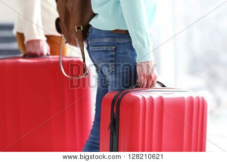 Couple carrying large red suitcases, close up