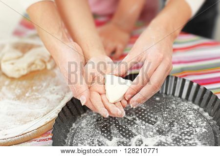 Mother and daughter cutting different cookie shapes