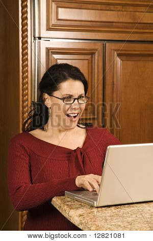 Caucasian woman typing on laptop in kitchen and looking at monitor with shocked expression.