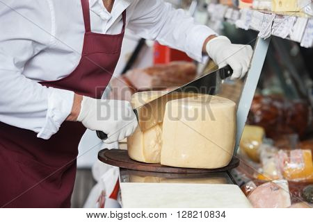 Salesman Slicing Cheese With Double Handled Knife