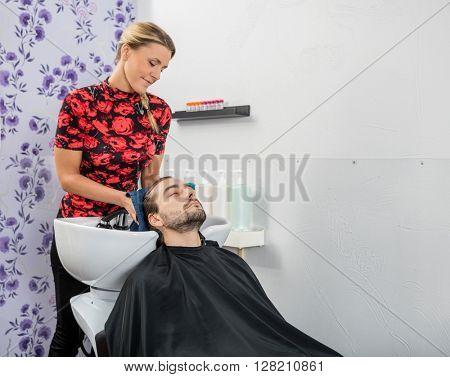 Beautician Drying Male Customer's Hair In Salon