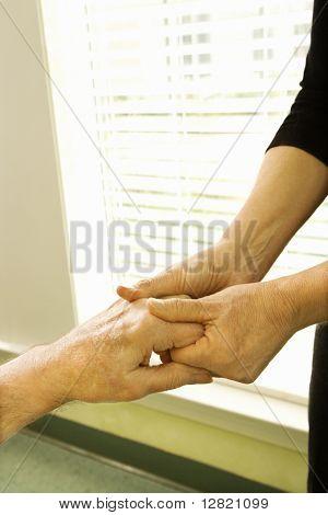 Caucasian female nurse massaging arthritic hands of elderly man at retirement community center.