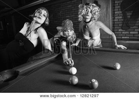 Three prime adult retro Caucasian females shooting pool.