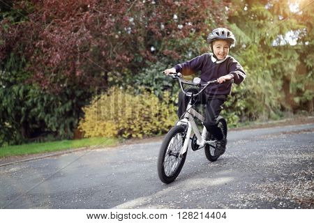 Boy learning to ride his bike home from school
