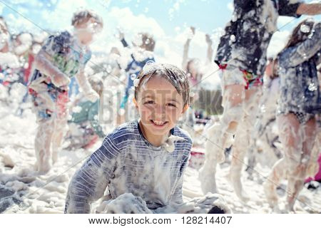 Boy smiling and laughing covered in soap suds at a summer foam party