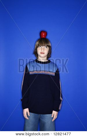 Portrait of Caucasian boy with an apple on his head standing against blue background.