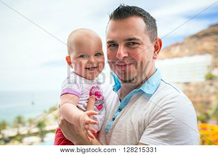 Happy baby girl with her father on holidays in Spain