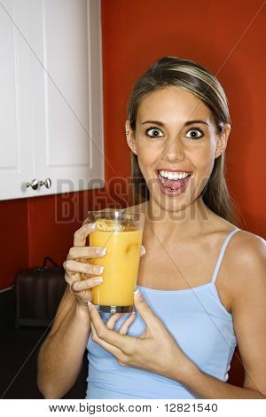 Portrait of young adult woman holding a glass of orange juice.