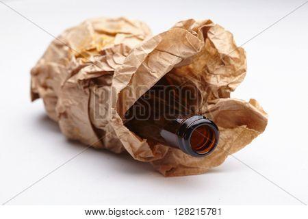 beer bottle inside a brown paper bag