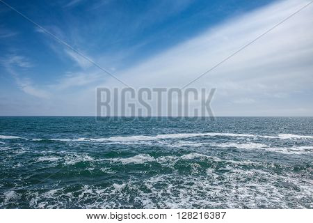 Blue sea with waves and sky with clouds