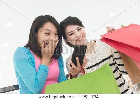 Excite women go shopping and use a smartphone in department store