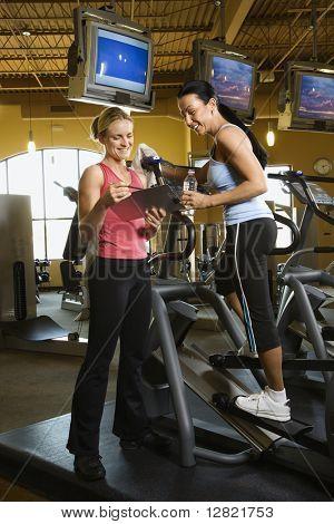 Primera hembra adulta caucásica en máquina elíptica en el gimnasio con entrenador.