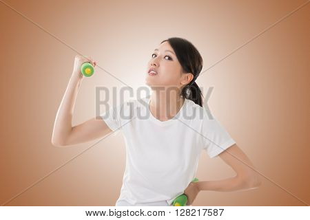 Funny Asian woman in sport holding dumbbell.