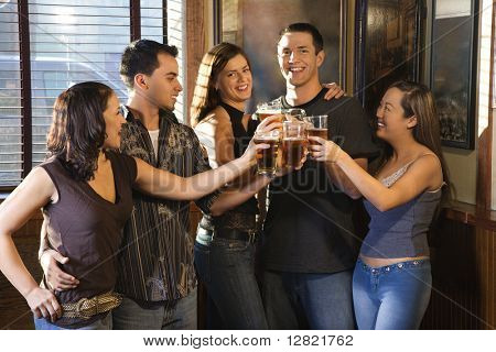Group of young friends hanging out in pub and toasting with their beers.