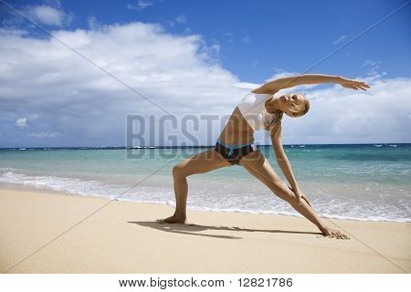 Caucasian young adult Woman Dehnung am Strand.
