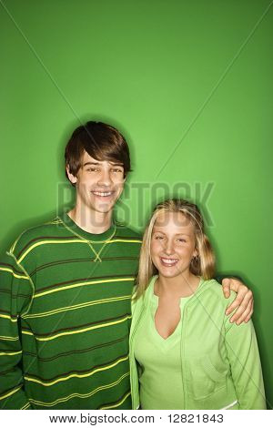 Portrait of Caucasian teen boy and girl standing against green background smiling with arms around eachother.
