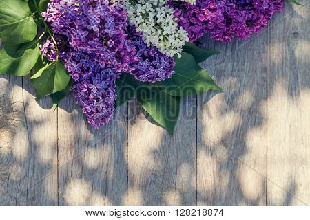 Colorful lilac flowers on garden table. Top view with copy space. Toned