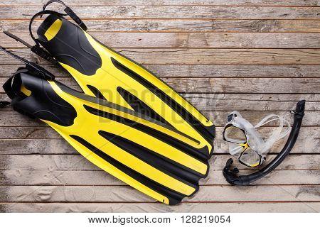 Mask, fins and snorkel on wooden desk