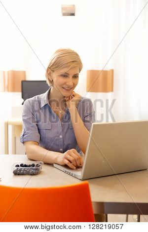 Attractive blonde woman working on laptop computer at home.