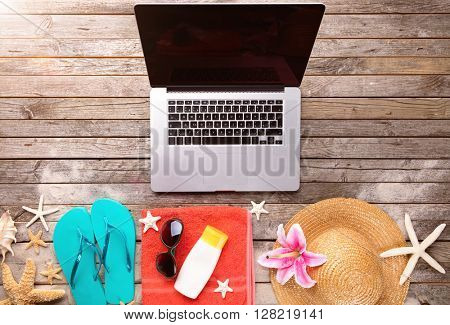 Laptop with beach accessories on wood deck