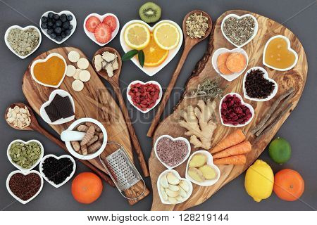 Large selection of cold and flu remedy super food and herbal medicine high in antioxidants and vitamin c on olive boards and spoons over grey background..