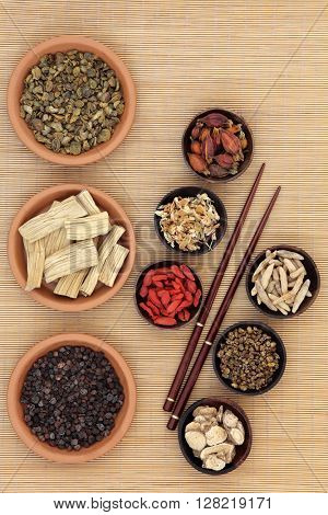 Chinese medicinal herb ingredients used in traditional herbal medicine over bamboo background.