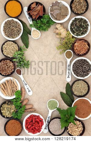 Medicinal herb and spice selection used in alternative medicine forming an abstract background on hemp paper.