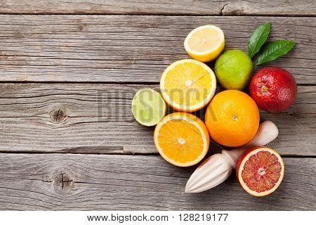 Fresh ripe citruses. Lemons, limes and oranges on wooden table. Top view with copy space