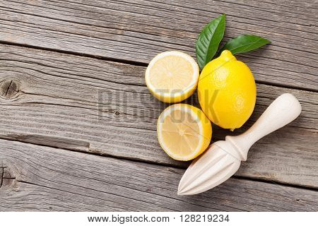 Fresh ripe lemons and juicer on wooden table. Top view with copy space