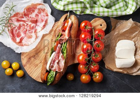 Ciabatta sandwich with romaine salad, prosciutto and mozzarella cheese over stone background. Top view