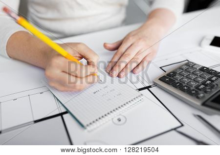 business, architecture, building, construction and people concept - close up of architect hand with blueprint and calculator writing to notebook