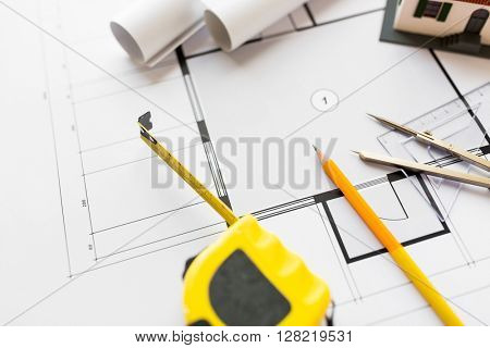 architecture, building, construction, real estate and home concept - close up of house blueprint and tools